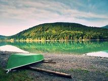 Abbandonato pescando il crogiolo di pagaia sulla banca del lago alps Lago morning che emette luce dalla luce solare Immagini Stock Libere da Diritti