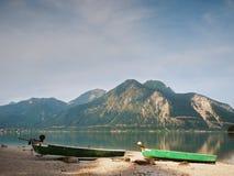 Abbandonato pescando il crogiolo di pagaia sulla banca del lago alps Lago morning che emette luce dalla luce solare Immagine Stock Libera da Diritti