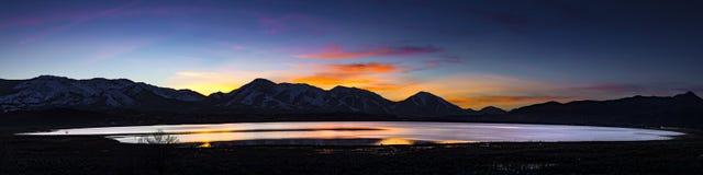 Abbandoni il lago, il playa sommerso al tramonto con le catene montuose e le nuvole variopinte Fotografia Stock