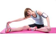 Abbastanza castana facendo l'allungamento del tendine del ginocchio sulla stuoia di esercizio Fotografia Stock Libera da Diritti