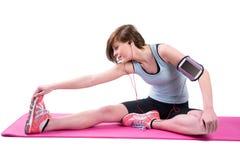 Abbastanza castana facendo l'allungamento del tendine del ginocchio sulla stuoia di esercizio Immagini Stock