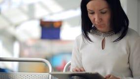Abbastanza castana si siede in aeroporto e nei giochi con il touchpad stock footage