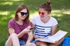 Abbastanza femminile con l'espressione positiva tiene lo Smart Phone, i surfes Internet, essendo nel buon umore, ha espressione p fotografie stock libere da diritti