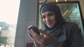 Abbastanza femminile nel hijab che applica polvere in caffè, sorridente in specchio, civetta video d archivio