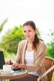 Abbastanza, giovane donna che per mezzo di un computer portatile a casa Immagini Stock Libere da Diritti