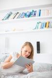 Abbastanza, giovane donna che si trova a letto, facendo uso del suo computer della compressa Fotografie Stock Libere da Diritti