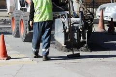 Abbau der Asphaltpflasterung auf der Straße beim Fahren von Maschinen mithilfe eines Minihydro-hammers während, Straße reparieren Stockfotos