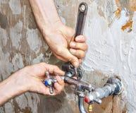 Abbau des alten fehlerhaften Hahns, Hände des Klempners mit Schlüssel Lizenzfreie Stockfotos