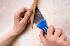 Abbau von alten Tapeten von der Wand Lizenzfreie Stockbilder