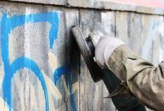 Abbau von Graffiti auf einer Betonmauer eines Untertagedurchganges mithilfe eines Winkelschleifers Stockbild