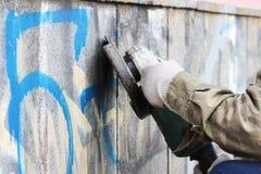 Abbau von Graffiti auf einer Betonmauer eines Untertagedurchganges mithilfe eines Winkelschleifers Stockfotos
