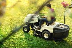 Abbellendo con l'erba della guarnizione dell'uomo mentre usando un lawnmow Fotografia Stock Libera da Diritti