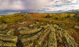 Abbellisca con il cielo tempestoso ed alloggi in montagne Immagini Stock Libere da Diritti