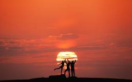 Abbellisca con la siluetta di una famiglia felice al tramonto fotografie stock libere da diritti