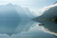 Abbellisca con le montagne che riflettono nell'acqua e nella piccola barca, Norvegia Fotografie Stock