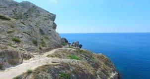 Abbellisca con le viste delle montagne, dei percorsi e del mare blu stock footage