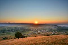 Abbellisca con nebbia, le colline e i moutains al tramonto Fotografia Stock