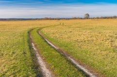 Abbellisca con una strada sterrata attraverso la marcita nella zona rurale vicino al villaggio di Mala Rublivka nel oblast di Pol Immagini Stock