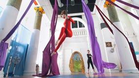 Abbellisca gli elementi perfoming della ginnasta della ginnasta dell'aria della donna sul cerchio aereo archivi video