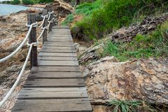 Abbellisca il ponte della spiaggia vicino al mare con le belle rocce della natura e Fotografia Stock