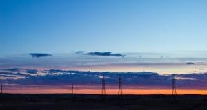 Abbellisca il tramonto sopra la strada ed il campo L'automobile sulla strada Fondo immagine stock