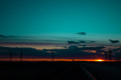 Abbellisca il tramonto sopra la strada ed il campo L'automobile sulla strada Fondo immagine stock libera da diritti