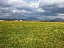 Abbellisca la foto di erba, di cielo blu, della nuvola e della montagna Immagini Stock