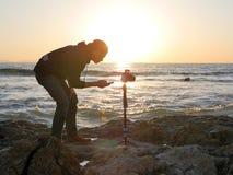 Abbellisca la fotografia sparata con il fotografo che installa la sua macchina fotografica su una spiaggia al tramonto Fotografia Stock Libera da Diritti