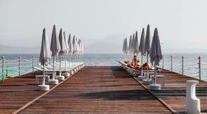 Abbellisca la polizia del lago con il pilastro, le sedie di spiaggia e gli ombrelli nella priorità alta, Italia Fotografia Stock