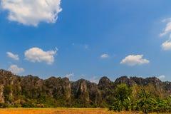 Abbellisca la vista della capanna dell'agricoltore nel giacimento del riso dopo raccolto con la gamma di montagne del calcare ed  Immagine Stock Libera da Diritti