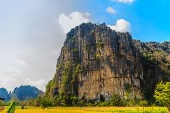 Abbellisca la vista della capanna dell'agricoltore nel giacimento del riso dopo raccolto con la gamma di montagne del calcare ed  Immagini Stock