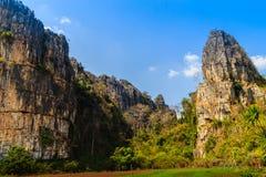 Abbellisca la vista della capanna dell'agricoltore nel giacimento del riso dopo raccolto con la gamma di montagne del calcare ed  Fotografie Stock