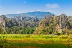 Abbellisca la vista della capanna dell'agricoltore nel giacimento del riso dopo raccolto con la gamma di montagne del calcare ed  Immagini Stock Libere da Diritti