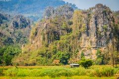 Abbellisca la vista della capanna dell'agricoltore nel giacimento del riso dopo raccolto con la gamma di montagne del calcare ed  Fotografie Stock Libere da Diritti