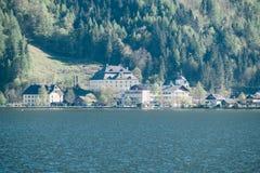 Abbellisca la vista delle case della città di Hallstatt con il lago e delle montagne austriache dell'alpe in Salzkammergut Fotografie Stock