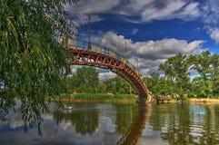 Abbellisca la vista di un ponte lungo sopra cielo blu e cada foresta Fotografia Stock