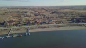 Abbellisca la vista superiore e una casa di campagna con i pilastri lungo il fiume stock footage