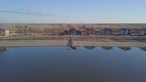 Abbellisca la vista superiore e una casa di campagna con i pilastri lungo il fiume video d archivio