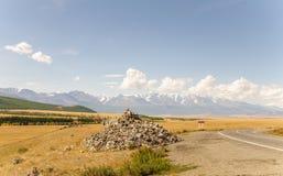 Abbellisca lo stepp con erba gialla asciutta e la gamma di alta montagna con i ghiacciai della neve ghiaccia, Altai, Russia Immagini Stock