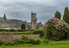 The Abbey Highland Club at Fort Augustus, Scotland. Fort Augustus, Scotland - June 11, 2012: Abbey Highland Club with clock tower fronted by garden with pink royalty free stock image