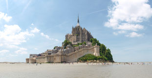 Abbey of Mont St. Michel. Mont St. Michel, France June 13, 2014: Abbey of Mont St. Michel. View of the Abbey from the sands at low tide. There are some unknown Stock Images
