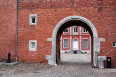 Abbey of Stavelot. Cobblestone road and gate to the main building of the Stavelot Abbey seen through a archway Stock Photo