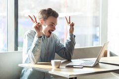Abbia idea! Il ritratto di giovani free lance barbute positive creative in camicia blu sta sedendo in caffè e sta lavorando al co immagini stock