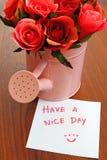 Abbia un giorno piacevole con le rose in latta di innaffiatura Fotografia Stock Libera da Diritti
