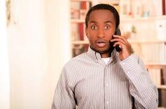 Abbigliamento casual d'uso dell'uomo bello che parla sul telefono cellulare mentre indicando il fondo ascendente e bianco degli s Immagini Stock Libere da Diritti