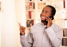 Abbigliamento casual d'uso dell'uomo bello che parla sul telefono cellulare mentre indicando il fondo ascendente e bianco degli s Fotografia Stock Libera da Diritti