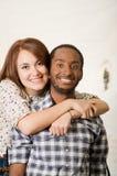 Abbigliamento casual d'uso delle coppie affascinanti interrazziali che posa abbraccio amichevole e sorridere, fondo bianco dello  Immagine Stock