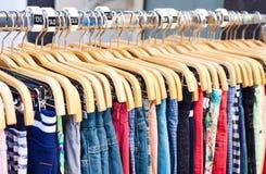 Abbigliamento casuale multicolore sui ganci di legno Fotografie Stock
