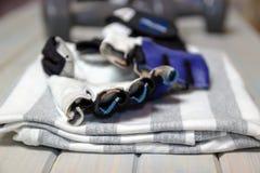 Abbigliamento di forma fisica Camicia, guanti su un fondo leggero di legno Oggetti per lo sport immagine stock libera da diritti