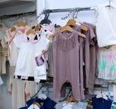 Abbigliamento di modo dei bambini sui ganci alla manifestazione immagine stock